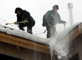(0183) Christopher Cisneros, left,  and Mario Lemus clear snow from the roof of The Dakota at...