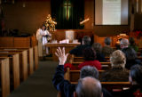 (PG7026) A member of the congregation raises her hand for a prayer request during the last service...