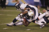 (0631) Josh Bell tackles LaDainian Tomlinson in the first quarter of the Denver Broncos against...