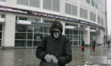 A homeless man who goes by the name Plague walks by the ticker outside the Denver Post and Rocky...