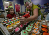 At Mulberries bakery owner Kathleen Karr fills a large order of cupcakes for a Christmas Party as...