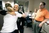 State Treasurer Mike Coffman (left) hugs accounting technician Julie Stephenson (cq, far left)...