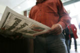 A customer reads the Rocky Mountain News as he waits in line to place his order at Heidi's Deli...