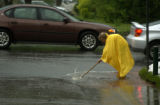 Elizebth Detine (CQ), 67, of Denver, tries to unclog a drainage ditch out in front of her home at...