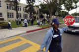 (Foreground) Cross guard Violeta Patterson (cq), mans traffic in front of Edison Middle School in...