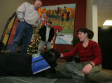 Linda Ruckle (r) working at the reception desk gives her dog Alpine, who is a medical service dog,...