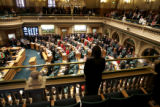 Visitors and members of the  Colorado House of Representatives, stand during taps, remembering...