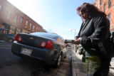 Officer Bonnie Medina (cq) issues a parking meter ticket to a car in the 1500 block  of Wazee...