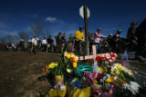 Dozens of bikers ride past one of many make-shift memorials setup for John Breaux (cq), the...