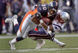Denver Broncos wide reciever, Rod Smith, left get pulled down by New England's Duane Starks,right,...