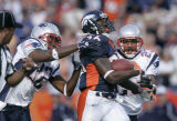 Tatum Bell is tackled by Asante Samuel, left, and Duane Starks, right, after a 68-yard run in the...