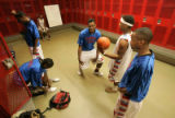 0164 Alphanzo Parks, third from right, tells a joke in the locker room to his fellow teammates as...