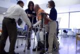 Donald Roberts gets help walking on his new prosthetic legs at Spalding Rehab Hospital in Aurora...