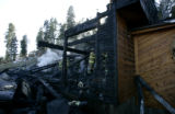 Firefighters from Elk Creek and Evergreen Fire Districts water hot spots on a home that was...