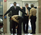 NBA star Kobe Bryant, left, and defense attorney Hall Haddon are searched by sheriff's deputies as...