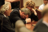 Michael Blagg, center, rests his head on his hands while sitting with his defense attorney, David...