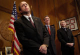 U.S. Attorney John Suthers, left, flanked by Gov. Bill Owens, center, and outgoing Attorney...
