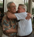 Victim family members Roy Sells, left, and Charles Tomlin hug each other outside of the U.S....