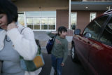 Akie Teters (cq) and her son Andrew, 11 (cq) carry their groceries in a reusable bag as they leave...