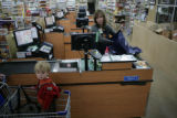Spencer Francisco, 18 months, (cq) stands in a shopping cart while his mother's groceries are...