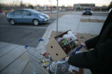 d'Armond Speers (cq) of Thornton pushes his groceries to his car after shopping at Vitamin Cottage...