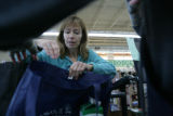 Sandra Clark (cq) helps Stephanie Lucero (cq) to load her groceries into a reusable bag at Vitamin...