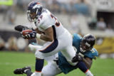 The Denver Broncos' Kyle Johnson (#39, FB) tries to slip the tackle of the Jacksonville Jaguars'...