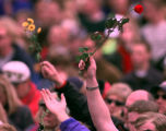 RMN123-DENVER,CO.- 4-25-99-Mourners raise their flowers to the sky while listening to Christian...