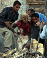 NYT10 - (NYT10) BAGHDAD, Iraq -- June 14, 2004 -- IRAQ-1 -- A crowd of Iraqis carry an injured man...