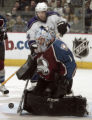 Avalanche goaltender David Aebischer,bottom, makes good on a save in the second period of play as...
