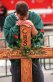 RMN154-DENVER,CO.- 4-25-99- An unidentified mourner leans on a cross at the  memorial service...