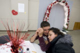 DM0214  Maria Gomez, 27, snuggles with her fiance Uriel Rodriguez, 20, as they wait for their...