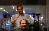 Philip Fiore trims  20 years customer Greg Dormaier's hair at his salon in Denver, Colo. Thursday,...