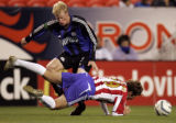Colorado Rapids defensive forward, Nat Borchers,left, tries to avoid getting tripped up as Chivas...