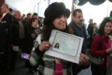 Shiva Nasab from Denver, holds up her certificate of citizenship as her husband takes her photo...