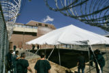Sheriffs deputies, inmates, and jail maintenance workers raise a 40 by 60 foot tent in an exercise...