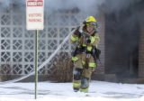 As smoke billows behind him, a Grand Junction firefighter pulls a hose to a different spot to...