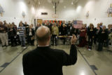 462 Doug Hartmann, CQ, GOP captain for precinct 52, holds an American flag so that those who...