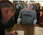 Bryce Givens smiles as his father Brian Givens signs his paper at Mullen HS in Denver, Colo....