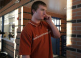 Nolan Brewster chats on the phone after signing with UT at Mullen HS in Denver, Colo. Wednesday,...