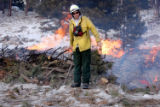 Fuel Specialist Doug Watry warms up in front of a traditional pile burn at the Moraine Park...