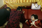 [0012] Eileen Wang, 2, watches as her mother Jiu Mei Ruan and father Sam Wang (cq) pray during the...