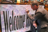 Rep. Ken Summers (cq) R-Lakewood, signs a banner to welcome back Rep. Joe Rice (cq) D- Littleton,...