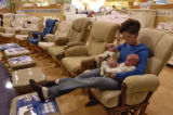 Jennifer Dunne (cq) sits with her twins, Devon and Braydon, left to right, in a store called...