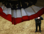 A police officer takes a quiet moment to honor the pledge of allegiance to the flag, at the start...
