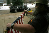 Steven Marsh (cq), a member of the Patriot Guard Riders removes one of the dozens of American...