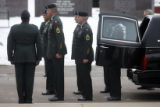 Members of the honor guard stand next to the hearse containing the casket of Major Andrew Olmsted,...