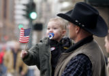 Charles Butterfield, from Byers, CO holds his young son Chaz as they watch the annual National...