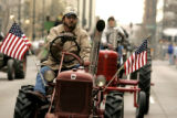 Rick Ausmus drives a 1948 Farmall Cub tractor in the National Western Stagecoach  down 17th Street...