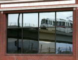 A Light Rail train is reflected in the window of the former Gates Rubber Administration building,...